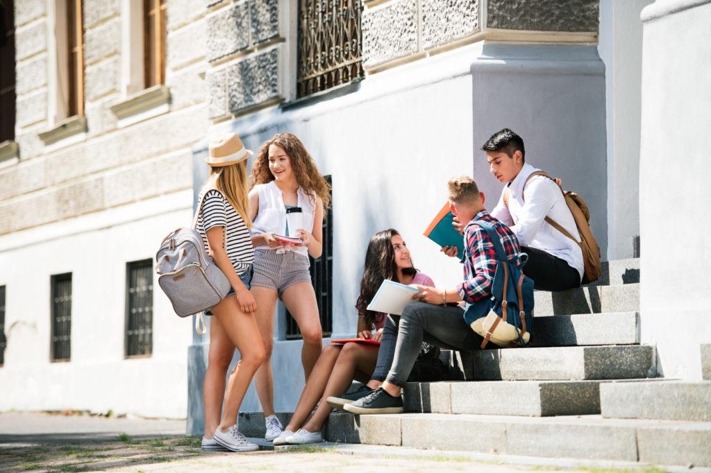 Studenten sitzen auf einer Treppe und unterhalten sich miteinander