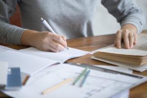 Frontalansicht einer Studentin die am Schreibtisch sitzt und lernt. Mit der einen Hand schreibt sie, während die andere Hand auf einem aufgeschlagenen Buch liegt.