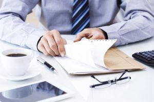 Ein Geschäftsmann sitzt an einem weißen Tisch und blättert in einer Akte. Auf dem Tisch befindet sich außerdem eine Tasse Kaffee, ein Kugelschreiber, ein Tablet, eine Brille und eine Computertastatur.