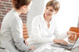 Managerin zeigt einem Kunden die Informationen auf dem Laptop an.