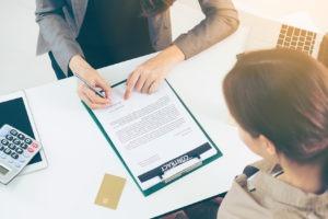 Das Bild zeigt zwei Geschäftsfrauen die einen Vertrag unterzeichnen.