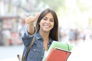 Lachende Studentin zeigt einen Daumen nach oben und schaut dabei in die Kamera.