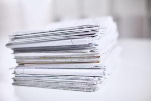 Ein großer Stapel Dokumente auf einem weißen Tisch