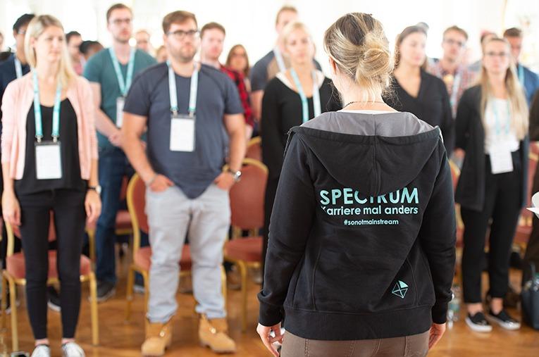 SPECTRUM Mitarbeiterin steht mit dem Rücken zum Betrachter gekehrt vor einer großen Menge weiterer SPECTRUM Mitarbeiter und erläutert verschiedene Entspannungsübungen