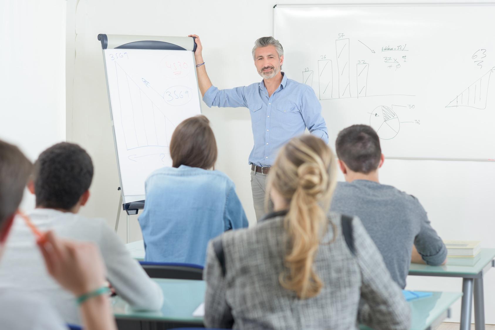 Ein Trainer mit Flipchart steht im Schulungsraum vor seinen Trainees.
