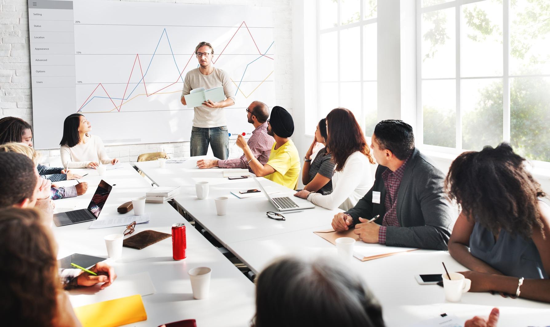Mehrere Seminarteilnehmer sitzen an einem Konferenztisch und folgen einer Präsentation.