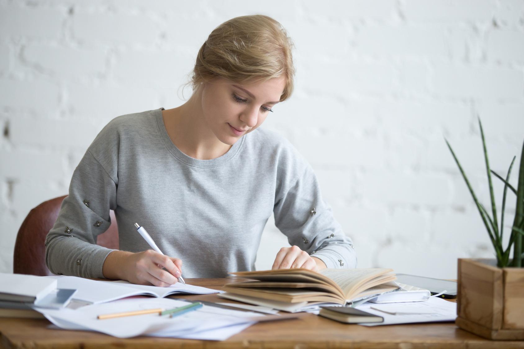 Eine junge Studentin beim Lernen an ihrem Schreibtisch. Sie schreibt, während sie in einem offenen Buch liest.