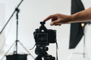 Im Zentrum des Bildes steht eine Digitalkamera inmitten eines professionellen Fotostudios. Von rechts ragt eine Hand ins Bild, die auf die Digitalkamera tippt.