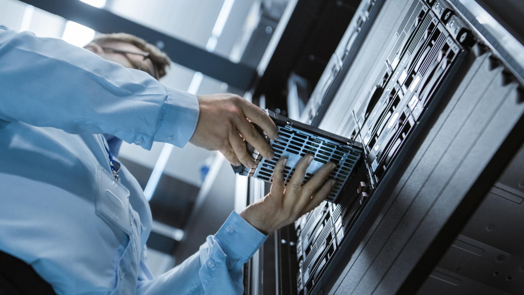 Ein IT Systemadministrator der gerade eine Festplatte wechselt.