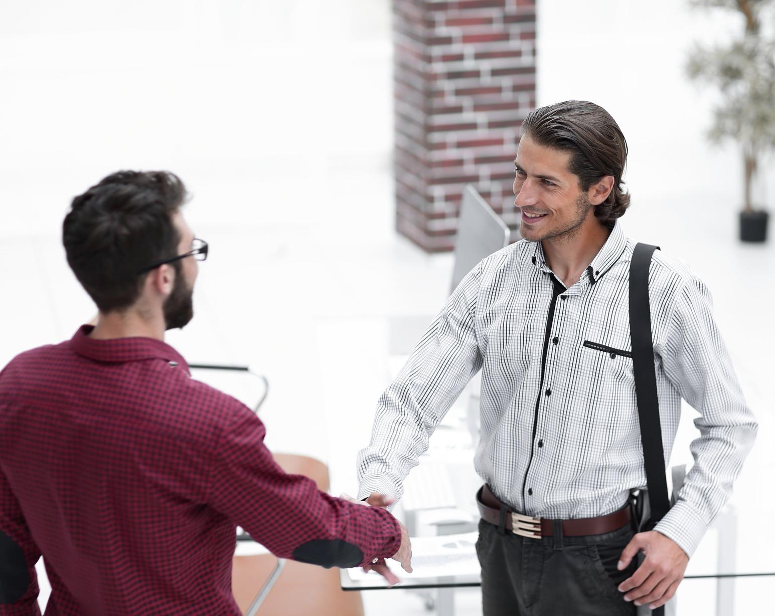 Junger Bewerber beim Handshake vor dem Vorstellungsgespräch.
