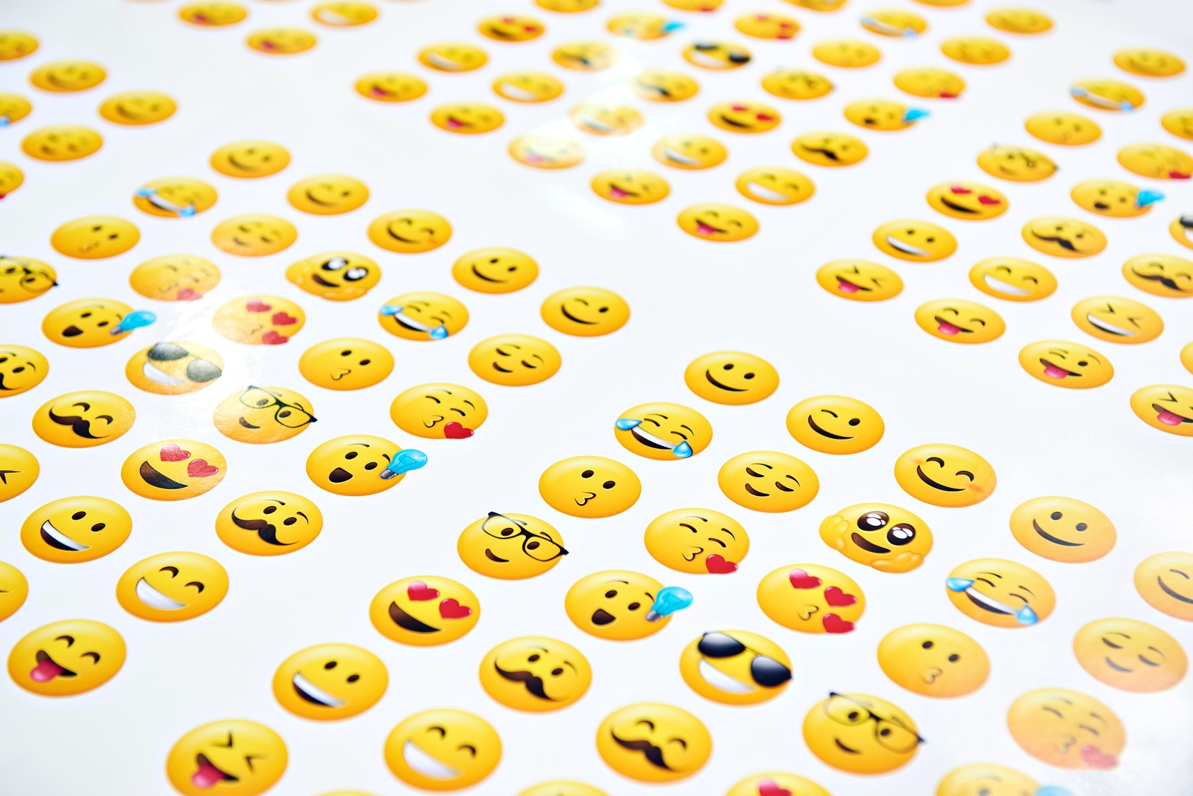 Große Ansammlung verschiedener Smiley Emojis, gedruckt auf weißes Papier.
