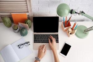 Vogelperspektive gerichtet auf einen Laptop der zwischen verschiedenen Büro-Utensilien auf einem Schreibtisch steht. Zwei Hände ragen ins Bild und tippen am Laptop.