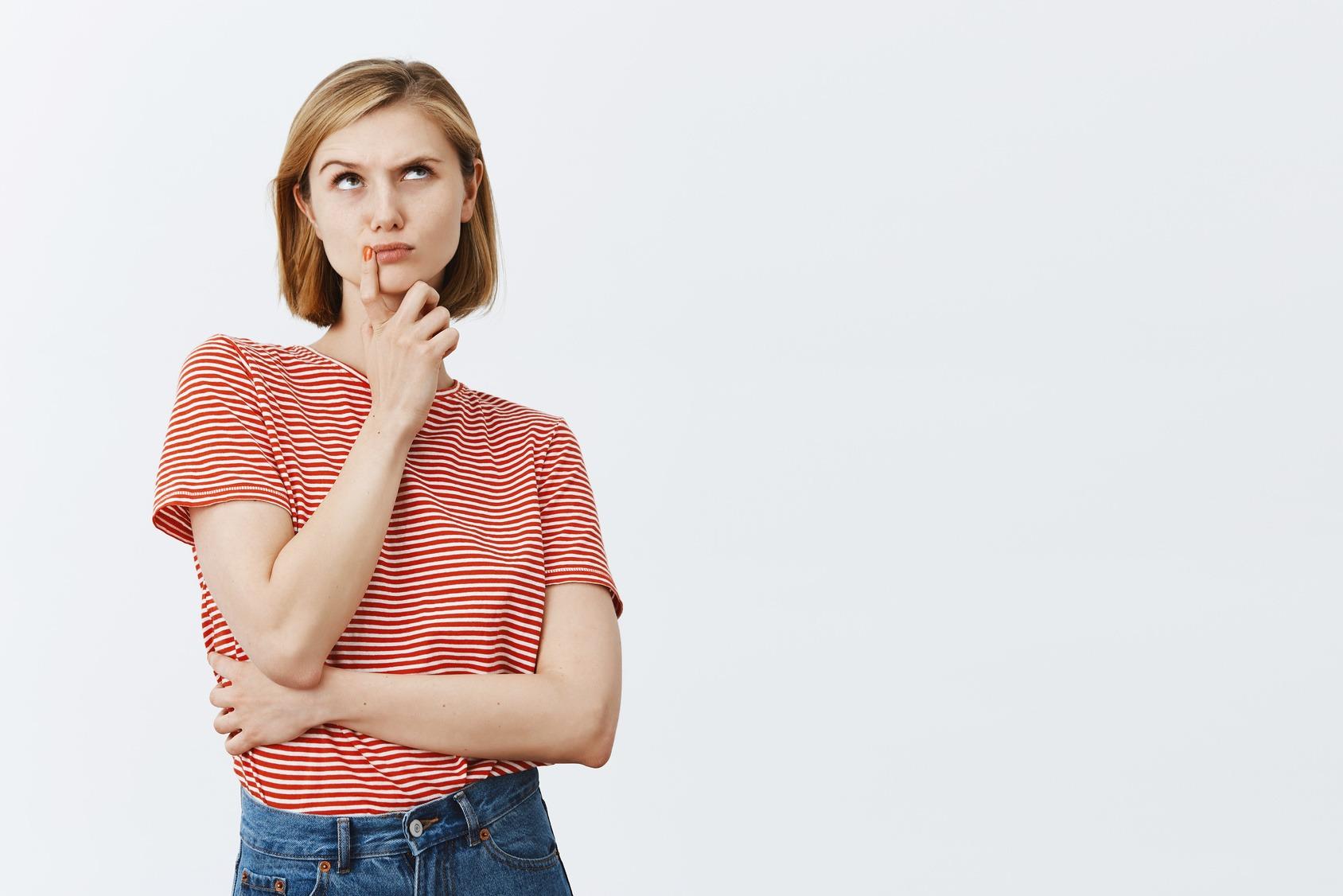 Junge Bewerberin macht die Denker Geste. Eine Augenbraue hochgezogen, der Blick geht nach oben und der Zeigefinger der rechten Hand liegt seitlich auf den Lippen.