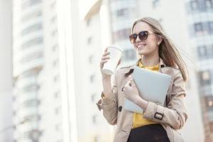 Das Bild zeigt eine lächelnde Studentin. In einer Hand hält sie einen Kaffeebecher, in der anderen Hand ein Tablet. Im Hintergrund sieht man eine Gebäudefront.