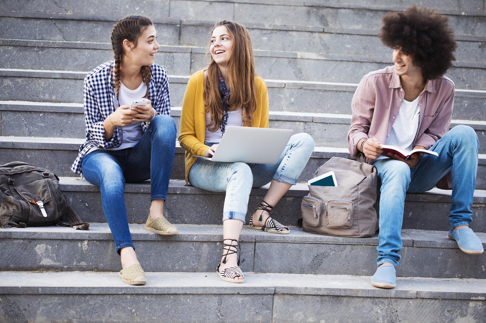 Drei junge Studierende sitzen auf einer Treppe und unterhalten sich. Neben und zwischen ihnen steht eine Umhängetasche und ein Rucksack.