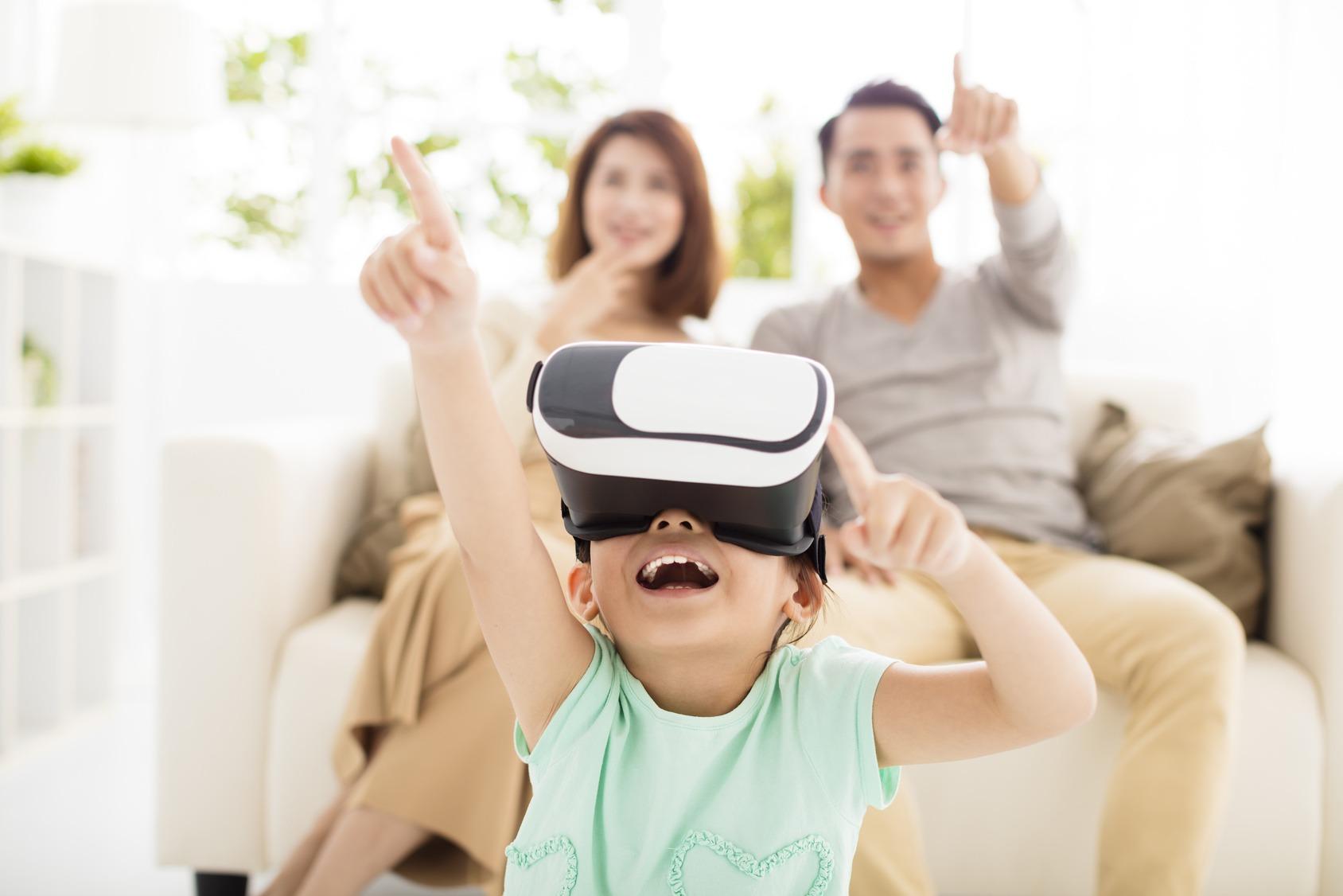 Eine junge Familie testet eine VR-Brille. Das Kind trägt die Virtual Reality Brille und sitzt im Vordergrund, die Eltern sitzen dahinter.