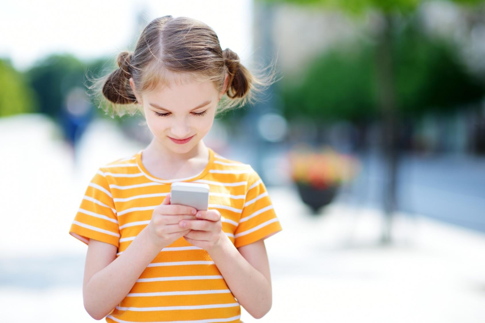 Junges Mädchen spielt mit einer Augmented Reality App auf ihrem Smartphone.