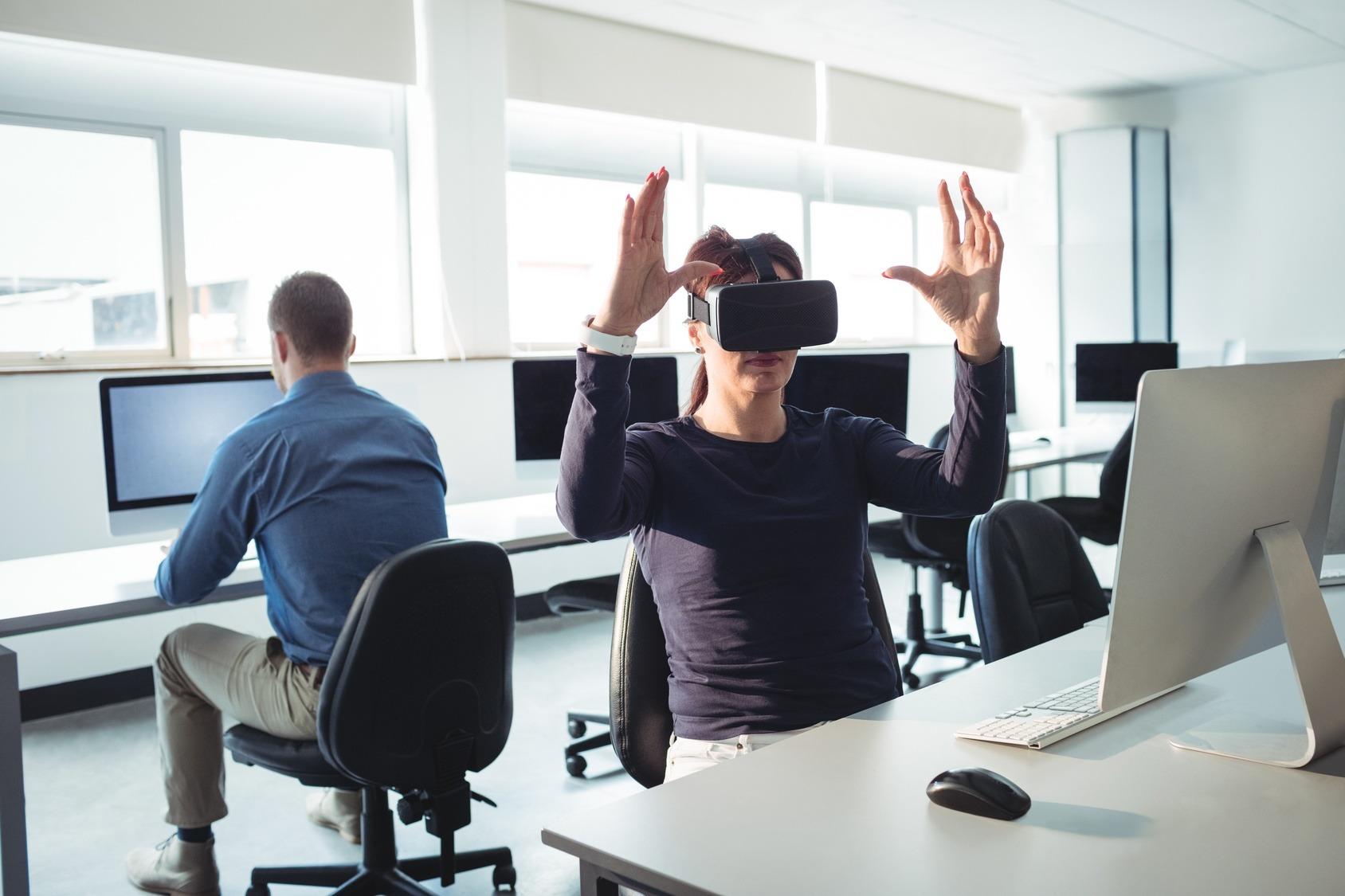 Eine Mitarbeiterin nutzt eine Virtual Reality Brille an ihrem Schreibtisch