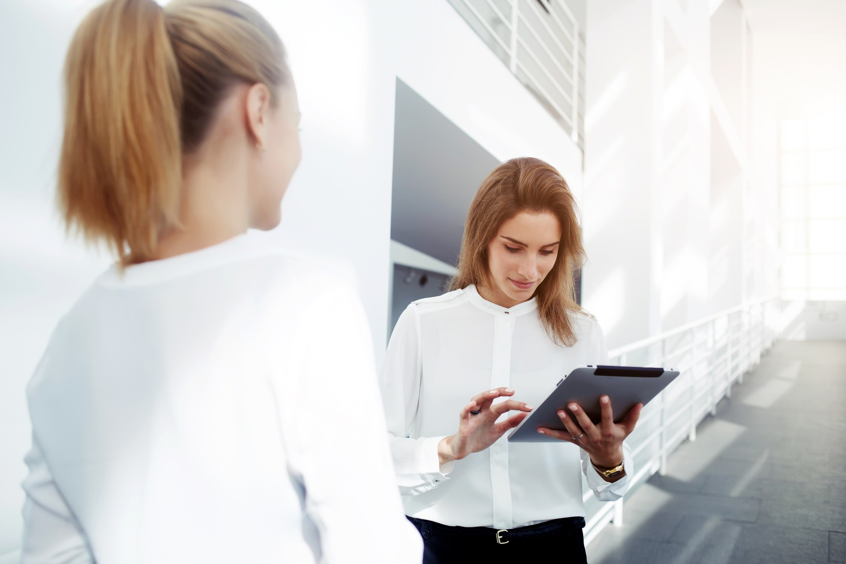 Zwei Studentinnen stehen sich in einem hellen Korridor gegenüber. Eine der Beiden hält ein Tablet.