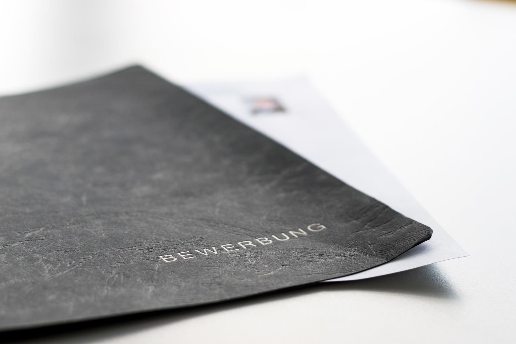 Eine schwarze Bewerbungsmappe liegt auf einem weißen Tisch.