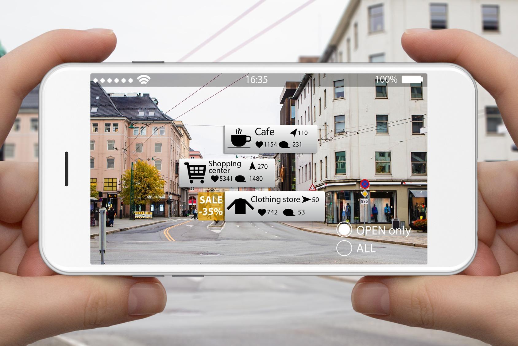 Ein Smartphone wird in Händen gehalten. Auf dem Display sieht man Echtzeitinformationen zu verschieden Geschäften und Attraktionen.