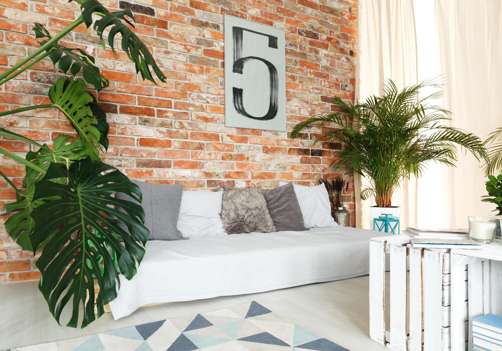 Wohnzimmer in einer stylischen Studenten-WG mit Blick auf ein Selbstgebautes Sofa vor einer Backsteinwand.