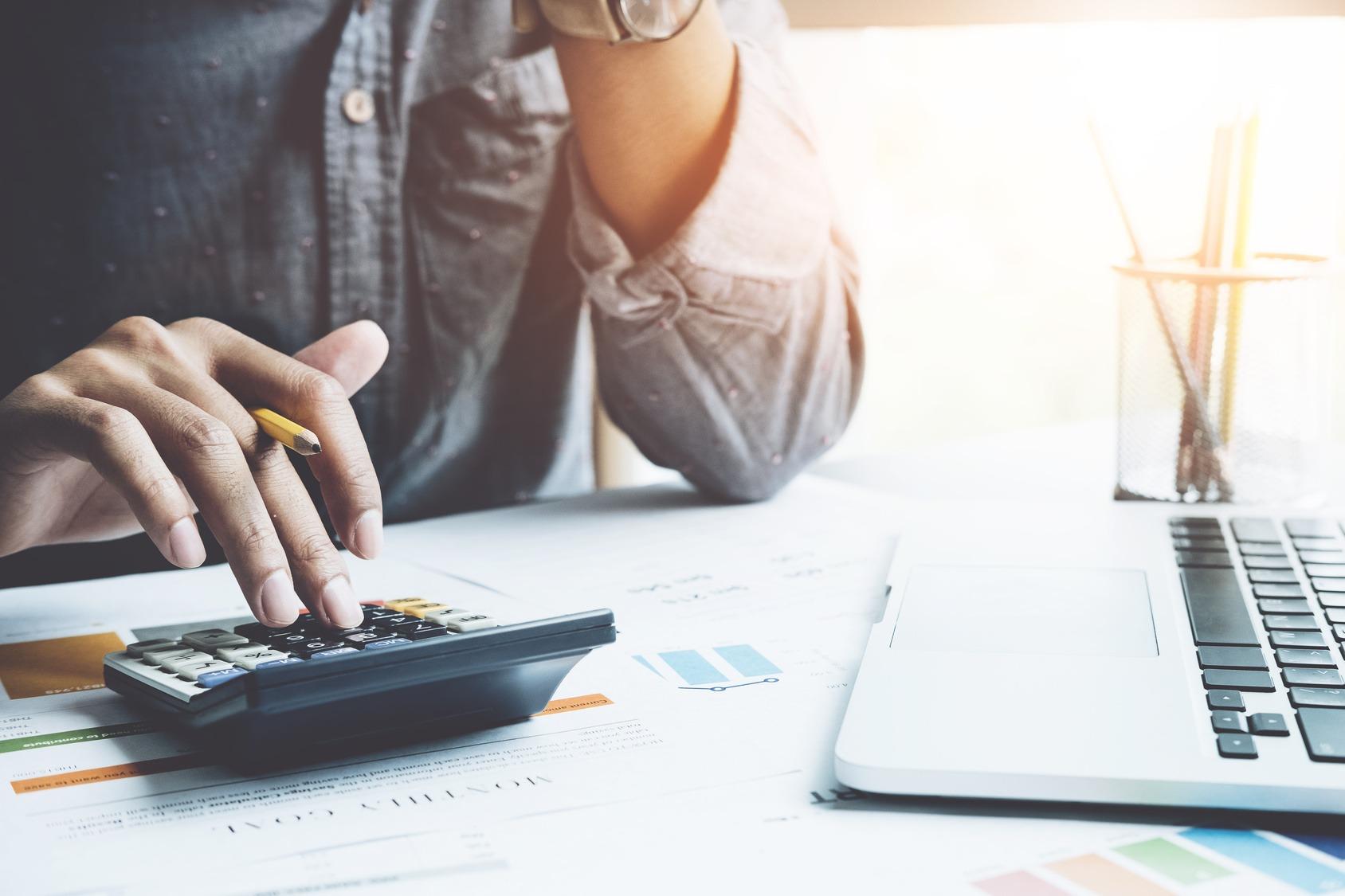 Ein Bewerber sitzt am Schreibtisch und berechnet etwas mit einem Taschenrechner. Nahaufnahme auf den Taschenrechner.