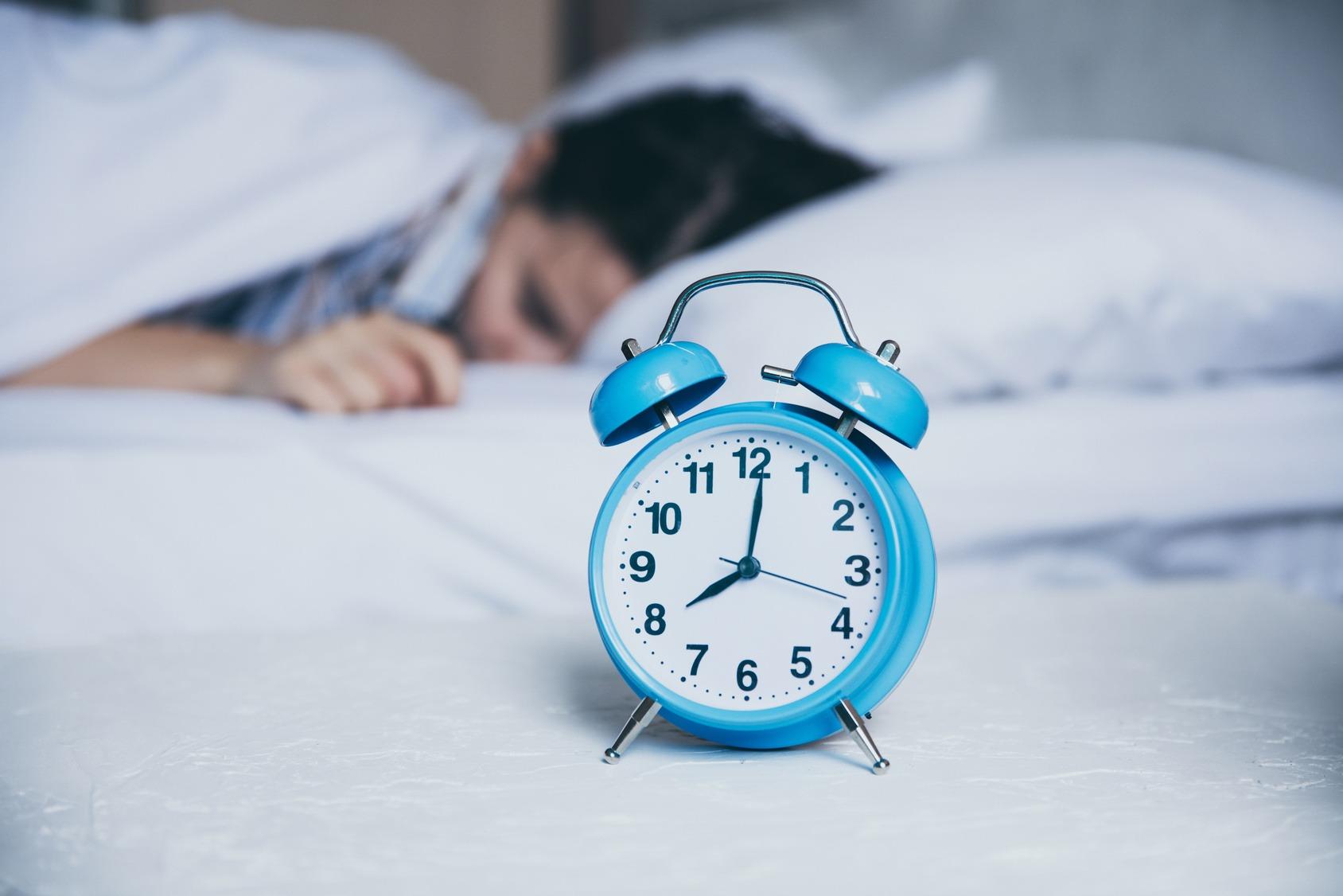 Im Vordergrund steht ein klassischer Wecker. Im Hintergrund liegt ein Student im Bett.