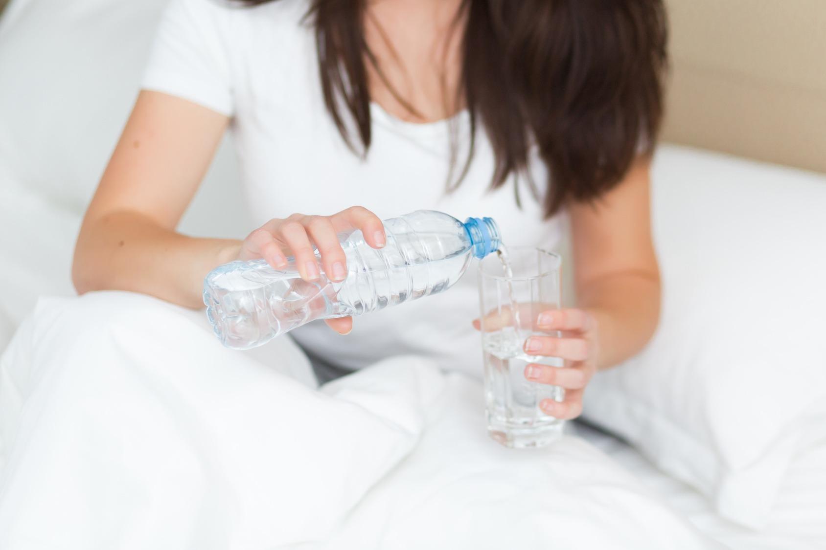 Junge Studentin sitzt nach dem Aufstehen im Bett und schenkt sich ein Glas Wasser ein.