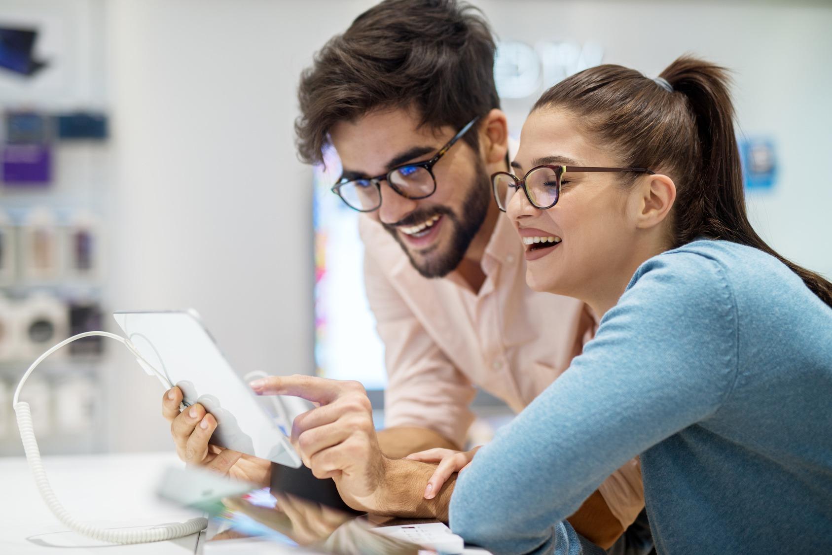 Ein junges Paar hat eine positive User Experience beim Testen eines neuen Tablets.