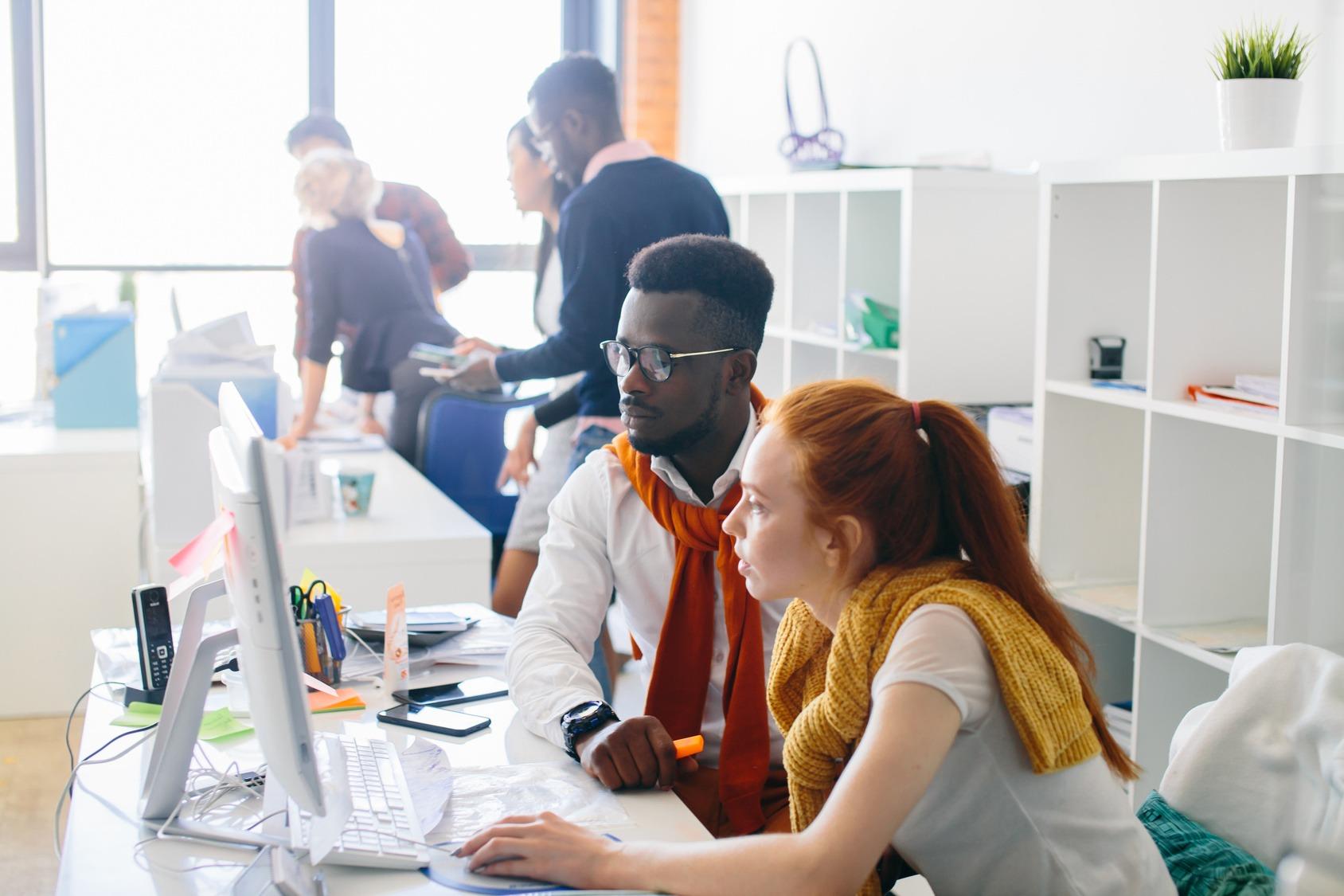 Eine neue Mitarbeiterin sitzt gemeinsam mit ihrem neuen Arbeitskollegen am Schreibtisch und wird eingelernt.