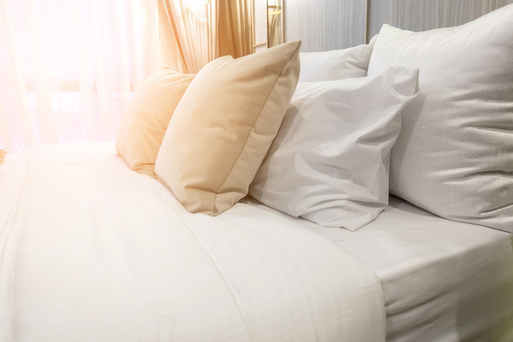 Frisch gemachtes Bett wird von der Sonne angestrahlt.