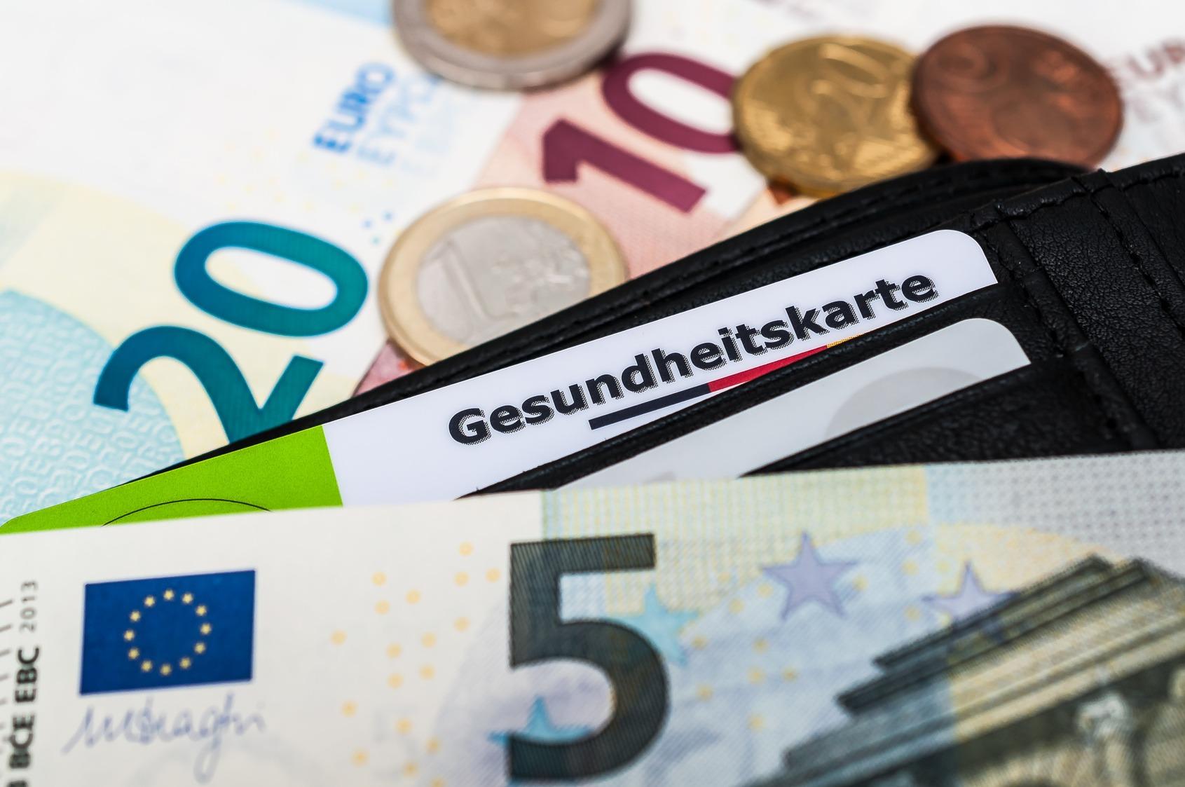 Zu sehen ist eine Gesundheitskarte einer Krankenversicherung, die in einem Kartenfach eines Geldbeutels steckt. Um den Geldbeutel herum liegen Euroscheine und Münzen.