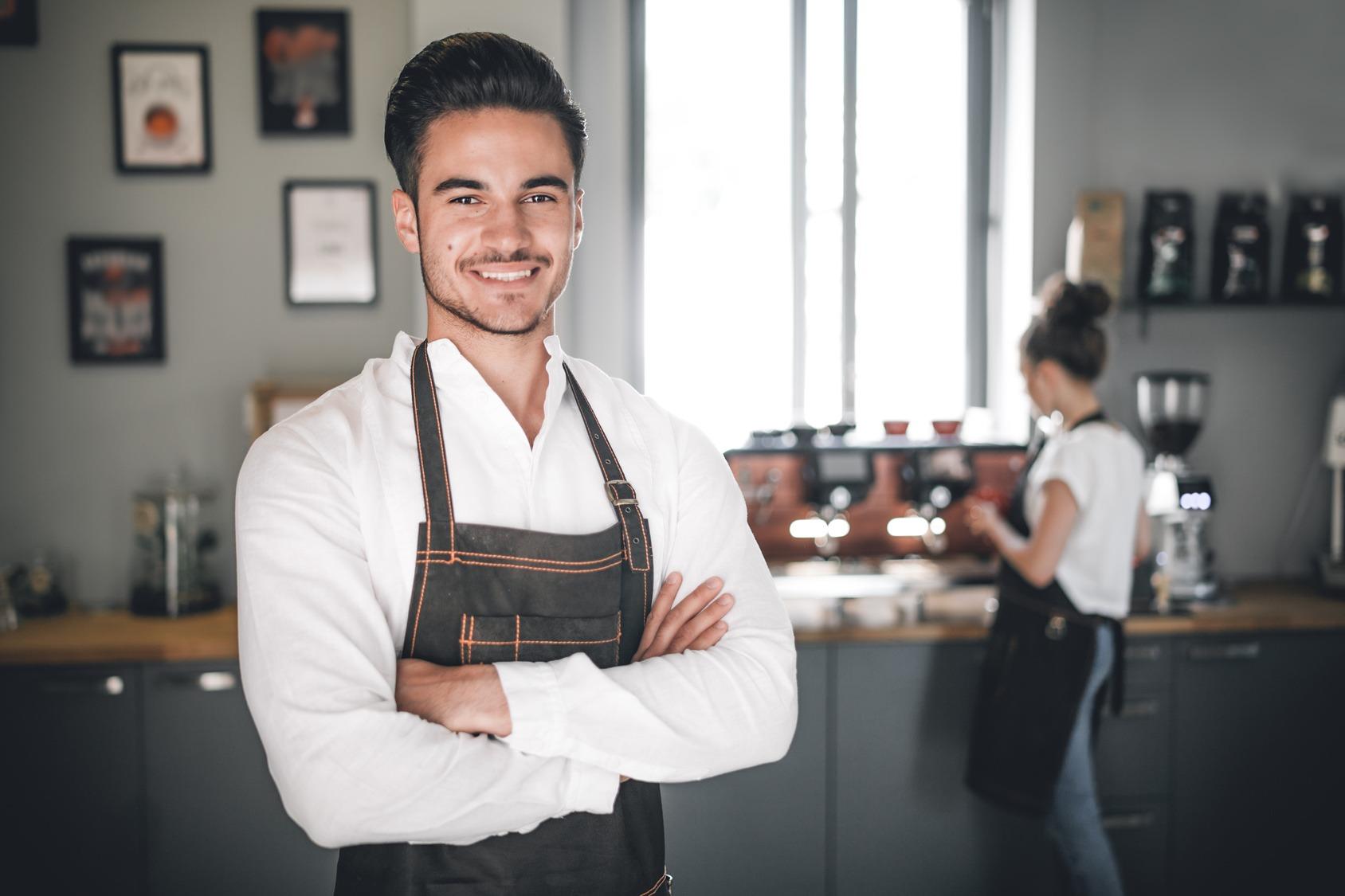 Ein zufrieden in die Kamera schauender Student bei seinem Nebenjob als Kellner in einem Cafe.