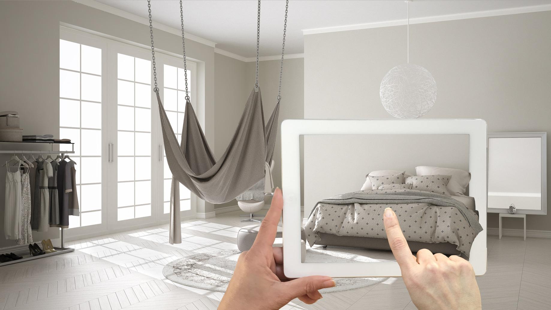Tablet mit Augmented Reality Anwendung mit der ein Bett im realen Zuhasue simuliert wird.