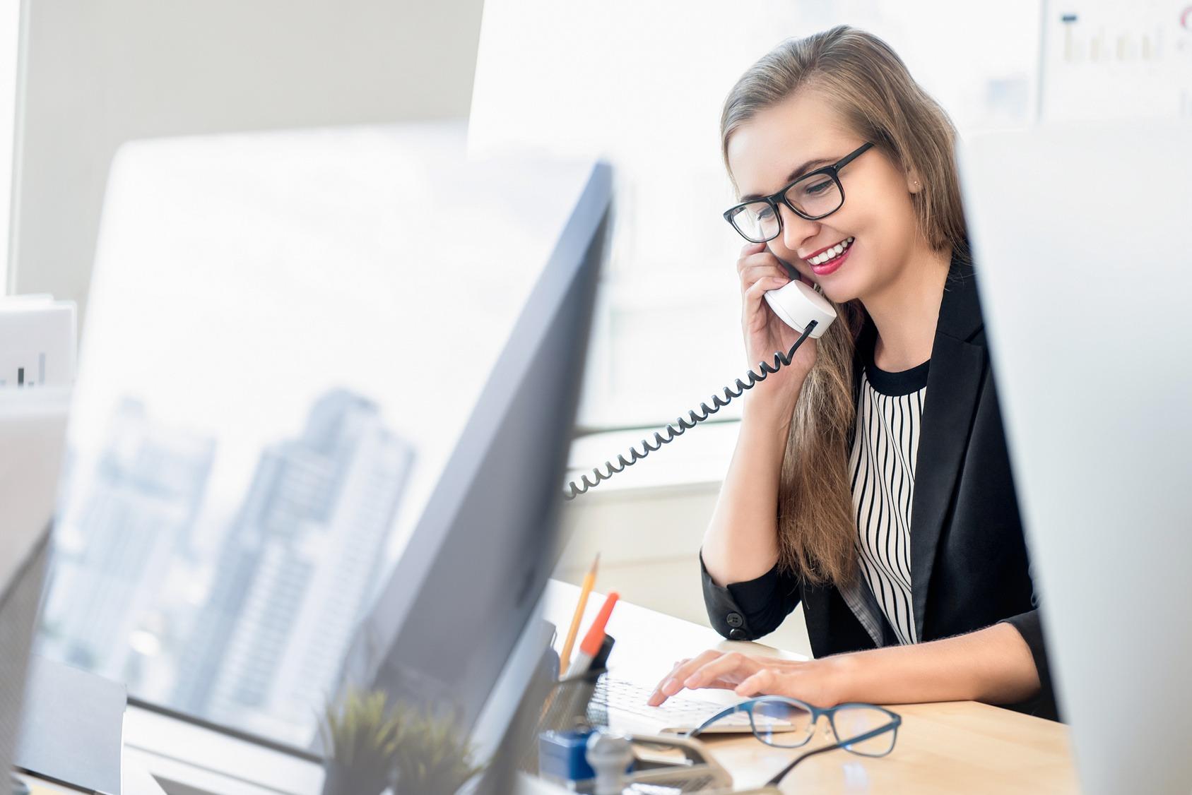 Die Teilnehmerin eines Traineeprogramms bei der Arbeit. Sie sitzt am Schreibtisch und tippt während sie telefoniert.