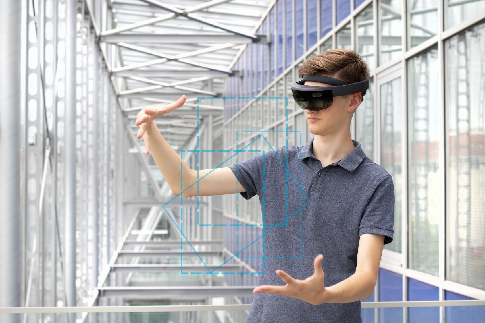 Junger Mitarbeiter mit Augmented Reality Brille formt virtuelle, geometrische Gebilde mit seinen Händen.
