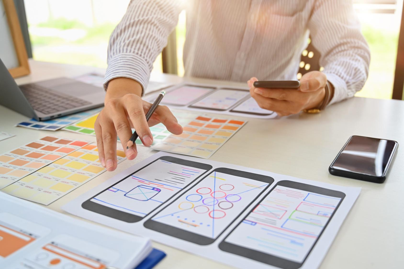 Ein UX Designer konzipert ein Layout für eine Web App am Schreibtisch. Er hat ein Smartphone und einen Stift in der Hand, vor ihm liegen Konzeptzeichnungen.