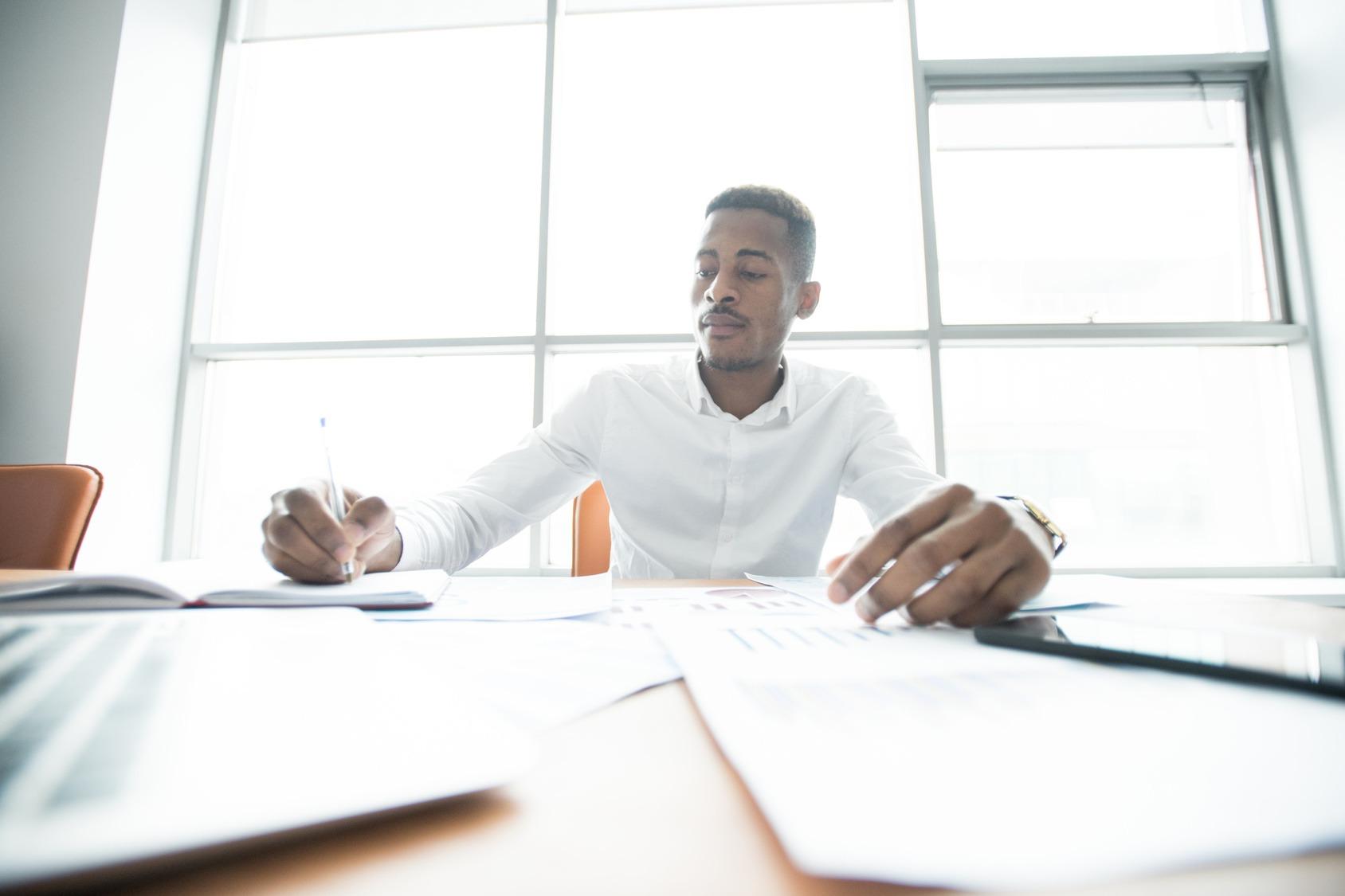 Beschäftigter Mitarbeiter notiert und liest am Schreibtisch während einer Trendanalyse.