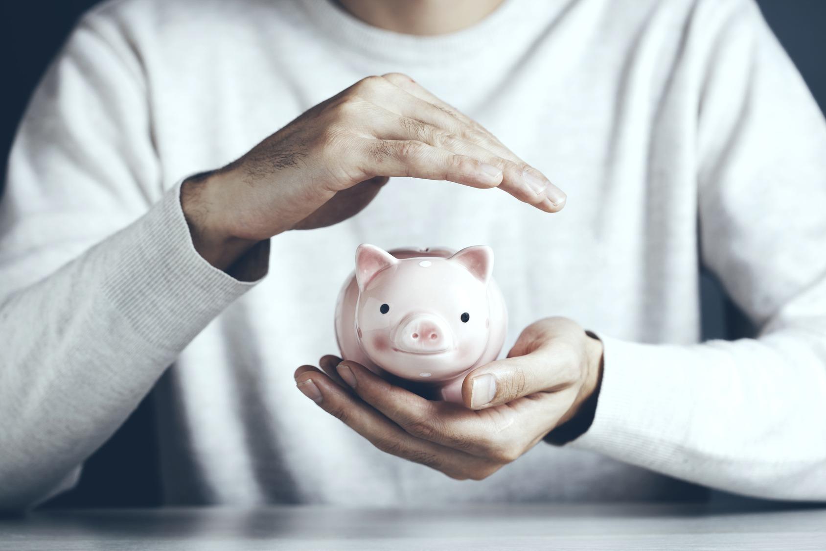 Ein Student hält ein Sparschwein in seiner linken Handfläche und hat seine rechte schützend darüber.