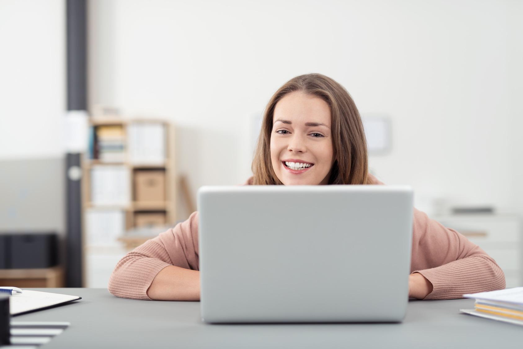 Studentin arbeitet am Notebook arbeitet am Notebook und freut sich, dass sie ihre Prokrastination besiegt hat