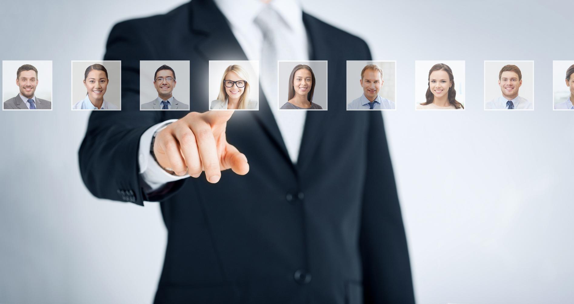 Im Vordergrund sieht man eine Reihe Profilbilder auf einem transparenten Band. Im Hintergrund steht ein Recruiter, der mit dem Finger auf das Profilbild einer jungen Frau zeigt.