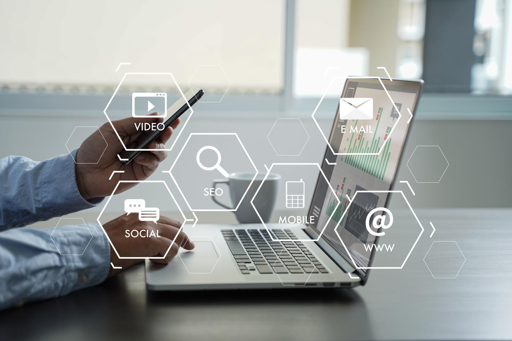 Recruiter analysiert Social Media Daten am Laptop. Im Vordergrund sind typische Interneticons zum Thema Video, SEO, Social Media, Mobile, Online und Email.