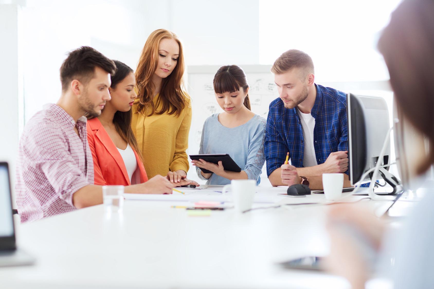 Fünf Studenten arbeiten konzentriert an zusammen.