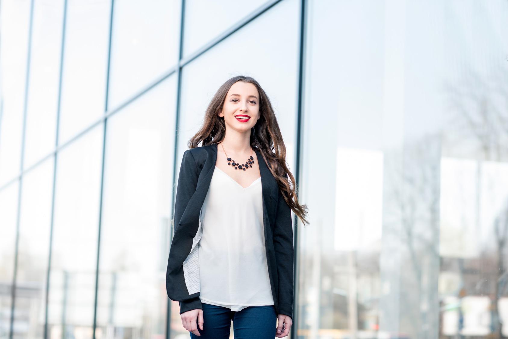 Eine junge Bewerberin läuft vor einer Glasfassade. Sie trägt eine weiße Bluse, Einen dunkelblauen Blazer und eine dunkelblaue Jeans.