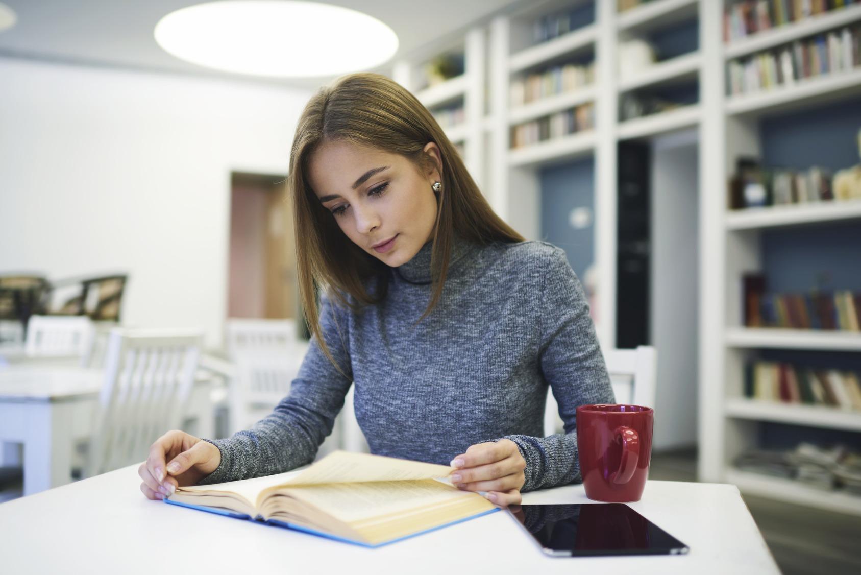 Junge Studentin lernt konzentriert in der Bibliothek.