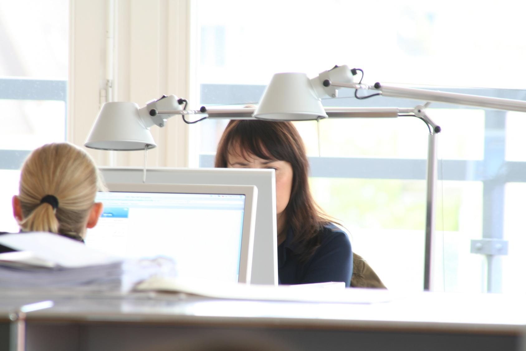 Zwei Kolleginnen sitzen an ihrem Schreibtisch und arbeiten konzentriert.