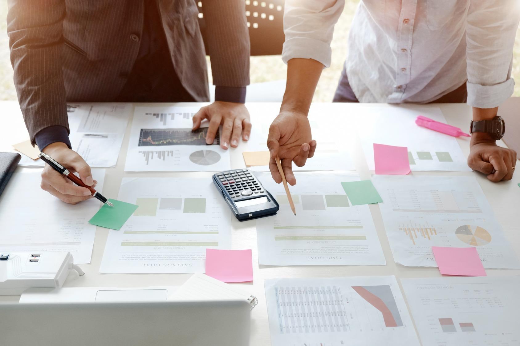 Zwei Business Analysten stehen vor einem Schreibtisch. Vor ihnen liegen mehrere Dokumente mit Diagrammen und Statistiken, außerdem ein Taschenrechner sowie ein Laptop.