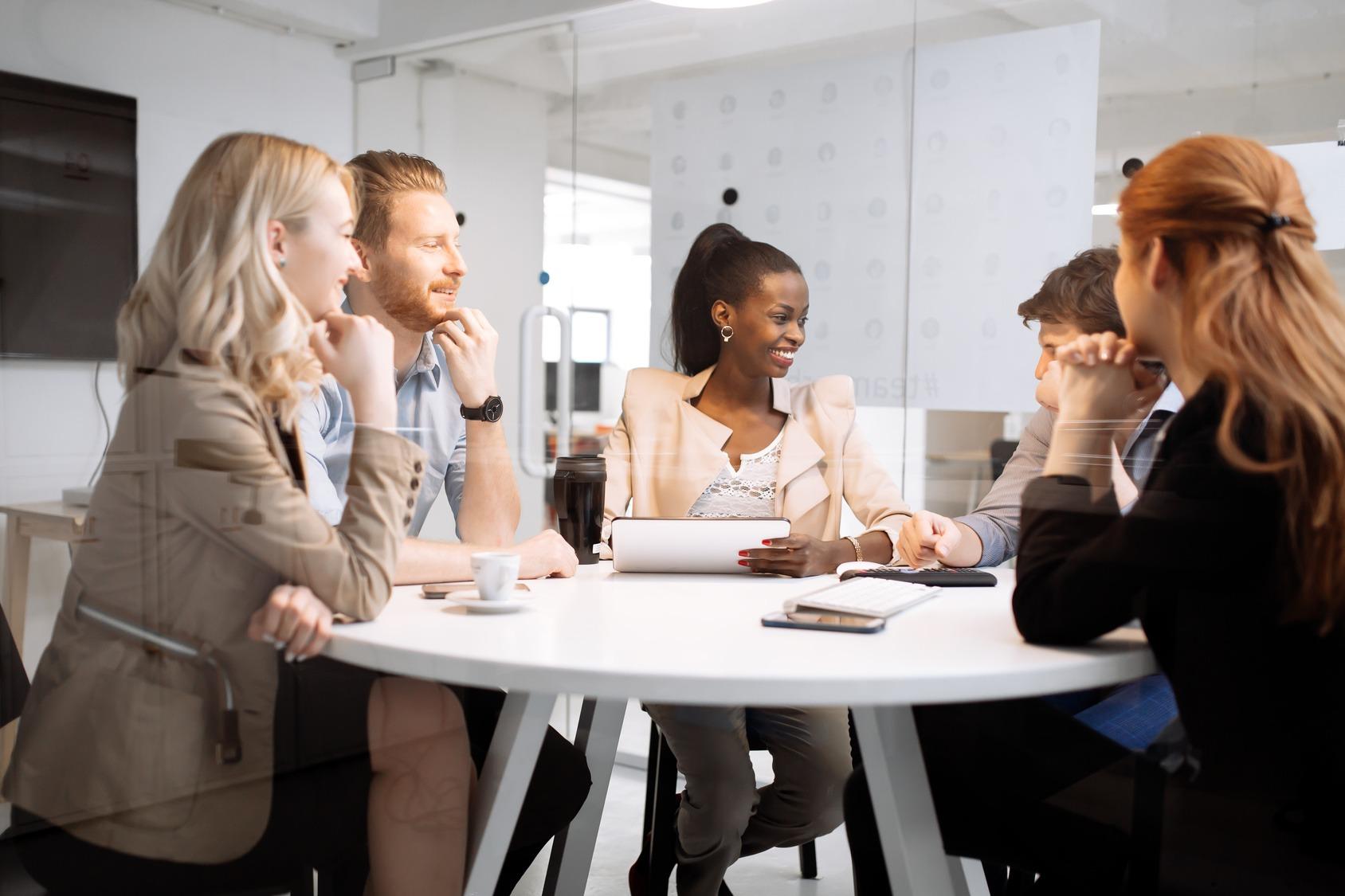 Fünf junge Geschäftsleute sitzen bei einem Meeting im um einen Runden Tisch