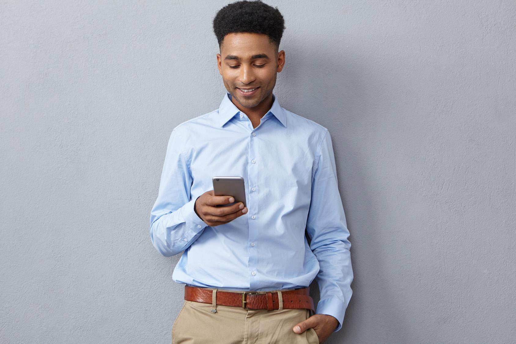 Gut gekleideter Bewerber mit Smartphone in der Hand. Er trägt ein hellblaues Hemd, eine hellbraune Chino mit braunem Gürtel